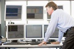 Έμπορος αποθεμάτων που εξετάζει τους μηνύτορες υπολογιστών Στοκ Φωτογραφία