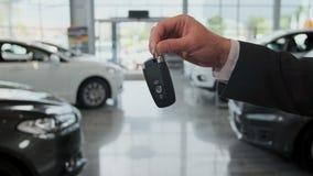 Έμπορος αυτοκινήτων που δίνει τα κλειδιά σε έναν πελάτη ενάντια στα αυτοκίνητα που σταθμεύουν απόθεμα βίντεο