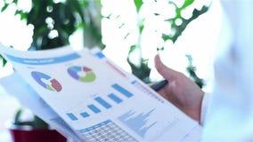 Έμπορος που αναλύει τα εισοδηματικά διαγράμματα φιλμ μικρού μήκους