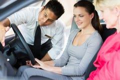 Έμπορος που εξηγεί στους πελάτες αυτοκινήτων Στοκ Εικόνα