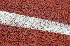 έναρξη Κόκκινη τρέχοντας πίστα αγώνων στο υπαίθριο αθλητικό στάδιο Στοκ εικόνες με δικαίωμα ελεύθερης χρήσης