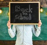 Έναρξη της έννοιας σχολικού έτους Ο δάσκαλος απρόσωπος κρατά τον πίνακα με τον τίτλο πίσω στο σχολείο Ο δάσκαλος κρατά τον πίνακα Στοκ φωτογραφία με δικαίωμα ελεύθερης χρήσης