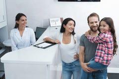 Ένας άνδρας και μια γυναίκα έφεραν ένα κορίτσι στον οδοντίατρο που συμπληρώνουν τη μορφή πριν από την υποδοχή Στοκ φωτογραφία με δικαίωμα ελεύθερης χρήσης