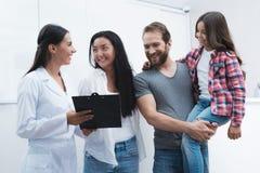 Ένας άνδρας και μια γυναίκα έφεραν ένα κορίτσι στον οδοντίατρο που συμπληρώνουν τη μορφή πριν από την υποδοχή Στοκ Εικόνα