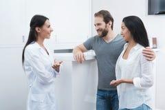 Ένας άνδρας και μια γυναίκα ήρθαν να δουν έναν οδοντίατρο που ο ρεσεψιονίστ συμπληρώνει τη μορφή και παίρνει συνέντευξη από τους  Στοκ εικόνες με δικαίωμα ελεύθερης χρήσης
