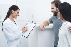 Ένας άνδρας και μια γυναίκα ήρθαν να δουν έναν οδοντίατρο που ο ρεσεψιονίστ συμπληρώνει τη μορφή και παίρνει συνέντευξη από τους  Στοκ Εικόνα