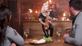 Ένας άνδρας και μια γυναίκα κατά μια ημερομηνία που ακούει τη ρομαντική μουσική saxophone απόθεμα βίντεο