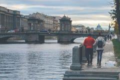 Ένας άνδρας και μια γυναίκα περπατούν κατά μήκος του αναχώματος ενός ποταμού Στοκ εικόνα με δικαίωμα ελεύθερης χρήσης