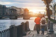 Ένας άνδρας και μια γυναίκα περπατούν κατά μήκος του αναχώματος ενός ποταμού Στοκ Εικόνα