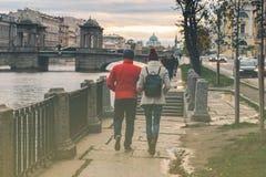 Ένας άνδρας και μια γυναίκα περπατούν κατά μήκος του αναχώματος ενός ποταμού Στοκ φωτογραφία με δικαίωμα ελεύθερης χρήσης