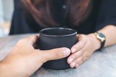 Ένας άνδρας και μια γυναίκα που κρατούν ένα μαύρο φλυτζάνι καφέ Στοκ φωτογραφία με δικαίωμα ελεύθερης χρήσης