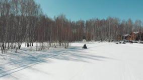 Ένας άνδρας οδηγά ένα τετράγωνο με μια γυναίκα σε έναν χιονώδη τομέα φιλμ μικρού μήκους