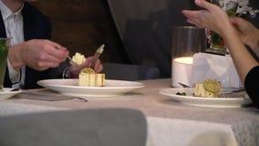 Ένας άνδρας που τρώει το κέικ με ένα δίκρανο, ένα τσάι κατανάλωσης γυναικών με το λεμόνι και τη μέντα απόθεμα βίντεο