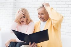 Ένας άνδρας σε μια κίτρινη ζακέτα και μια γυναίκα σε ένα ρόδινο πουλόβερ κάθονται και διαβάζουν τα έγγραφα σε έναν μαύρο φάκελλο Στοκ φωτογραφία με δικαίωμα ελεύθερης χρήσης