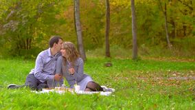 Ένας άνδρας φιλά μια γυναίκα στο πάρκο στο χορτοτάπητα απόθεμα βίντεο
