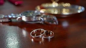Ένας άνδρας ` s και γαμήλια δαχτυλίδια γυναικών ` s Ένα άτομο ` s wristwatch είναι στο υπόβαθρο από την εστίαση απόθεμα βίντεο