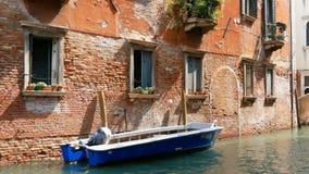 Ένας άνετος τοίχος ενός ενετικού σπιτιού τούβλου δίπλα σε μια σταθμευμένη βάρκα και της διάβασης από ένα κανάλι μιας άλλης βάρκας φιλμ μικρού μήκους