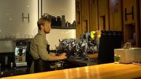 Ένας άνετος φραγμός καφέ όπου ένα γενειοφόρο barista προετοιμάζει τον καφέ, σε αργή κίνηση απόθεμα βίντεο