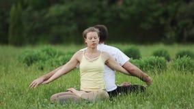 Ένας άνδρας και ένα τέντωμα γυναικών πρίν κάνει τις ασκήσεις Νέα πρακτική εκπαιδευτικών γιόγκας σε ένα πάρκο πόλεων στην πράσινη  φιλμ μικρού μήκους