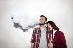 Ένας άνδρας και μια γυναίκα που καπνίζουν το ηλεκτρονικό τσιγάρο vape Στοκ Εικόνες