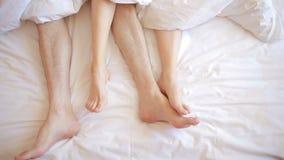 Ένας άνδρας και μια γυναίκα στο κρεβάτι αρσενική και θηλυκή τοπ άποψη ποδιών, άσπρα linens φιλμ μικρού μήκους