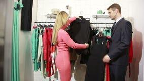 Ένας άνδρας περιμένει τη γυναίκα του επιλέγει ένα φόρεμα σε ένα κατάστημα άτομο που κρατά πολλά ενδύματα ο σύζυγος θέλει να φύγει φιλμ μικρού μήκους
