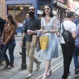 Ένας άνδρας σε ένα πουκάμισο καρό και μια γυναίκα σε ένα εκλεκτής ποιότητας μπλε φόρεμα με την κεντητική που περπατά κατά μήκος τ Στοκ εικόνα με δικαίωμα ελεύθερης χρήσης
