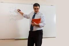 Ένας δάσκαλος μαθηματικών γράφει σε έναν πίνακα Στοκ Εικόνες