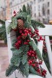 Ένας άσπρος ξύλινος πάγκος στο πάρκο είναι διακοσμημένος με τους κλάδους έλατου με τους κώνους και τα κόκκινα μούρα νέο έτος θέμα στοκ φωτογραφία με δικαίωμα ελεύθερης χρήσης