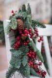 Ένας άσπρος ξύλινος πάγκος στο πάρκο είναι διακοσμημένος με τους κλάδους έλατου με τους κώνους και τα κόκκινα μούρα νέο έτος θέμα στοκ φωτογραφίες