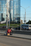 Ένας άστεγος τύπος κάθεται στο πεζοδρόμιο με ένα χαρτόνι και μια επιγραφή: εργασία ανάγκης Στο υπόβαθρο είναι ένα εμπορικό κέντρο Στοκ εικόνες με δικαίωμα ελεύθερης χρήσης