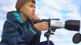 Ένας έφηβος κοιτάζει μέσω ενός τηλεσκοπίου απόθεμα βίντεο