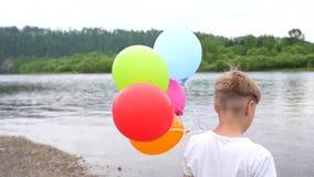 Ένας έφηβος κρατά τα μπαλόνια Καλοκαιρινές διακοπές στη φύση κοντά στη λίμνη Εορτασμός και διασκέδαση Γενέθλια παιδιών ` s απόθεμα βίντεο