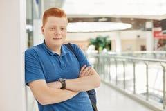 Ένας έφηβος με την κόκκινη τρίχα και φακίδες που φορούν την περιστασιακή μπλε μπλούζα και wristwatch που θέτουν στη λεωφόρο αγορώ Στοκ Εικόνες