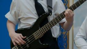 Ένας έφηβος σε ένα άσπρο πουκάμισο με τα κυλημένα επάνω μανίκια παίζει μια ηλεκτρική βαθιά κιθάρα Τα δάχτυλα του δεξιού είναι απόθεμα βίντεο
