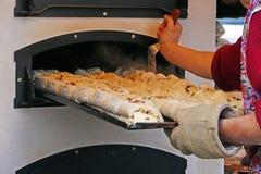 Ένας δίσκος του γεμισμένου ψωμιού ωθείται στο φούρνο ψησίματος Στοκ Εικόνα