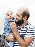 Ένας αγαπώντας πατέρας κρατά ένα παιδί στα όπλα του Συναισθηματική φωτογραφία στοκ εικόνα