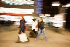 Ένας αγοραστής που περπατά μπροστά από την προθήκη στο σούρουπο Στοκ Φωτογραφία