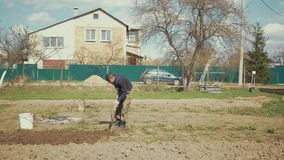 Ένας αγρότης που εργάζεται στον κήπο του απόθεμα βίντεο