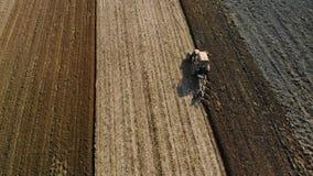 Ένας αγρότης σε ένα τρακτέρ προετοιμάζει το έδαφος για την πρόωρη εποχή άνοιξης Εργασία για τη αγροτική γη r απόθεμα βίντεο