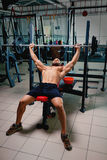 Ένας αθλητικός τύπος που κάνει την άσκηση με ένα μεγάλο barbell σε ένα φωτεινό υπόβαθρο γυμναστικής Μια κατάρτιση bodybuilder σε  Στοκ Εικόνες