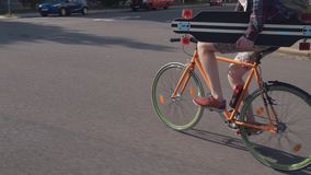 Ένας αθλητικός τύπος σε ένα ποδήλατο με ένα longboard κάτω από το βραχίονά του ορμά κάτω από την οδό πόλεων απόθεμα βίντεο
