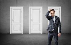 Ένας ανησυχημένος επιχειρηματίας αρπάζει το κεφάλι του με τρεις κενές άσπρες κλειστές πόρτες πίσω από τον Στοκ εικόνα με δικαίωμα ελεύθερης χρήσης
