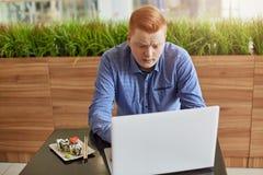 Ένας ανικανοποίητος νέος επιχειρηματίας με την κόκκινη τρίχα και το μοντέρνο κούρεμα που έχουν το μεσημεριανό διάλειμμα στο σύγχρ Στοκ Φωτογραφία