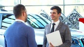 Ένας αντιπροσωπευτικός πωλητής δίνει τα κλειδιά αυτοκινήτων στον αγοραστή φιλμ μικρού μήκους