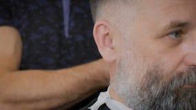 Ένας αξιοσέβαστος επιχειρηματίας με μια άσπρη γενειάδα στο σαλόνι για την τρίχα Η μοντέρνες χτένα και η περιποίηση κουρέων λειτου απόθεμα βίντεο