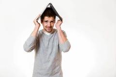 Ένας απελπισμένος νεαρός άνδρας κρατά το lap-top του ως στέγη πέρα από το κεφάλι του στοκ εικόνα