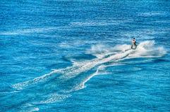 Ένας απομονωμένος αεριωθούμενος σκιέρ σπάζει το ήρεμο μπλε ωκεάνιο νερό σε μεγάλο Τούρκο Στοκ φωτογραφία με δικαίωμα ελεύθερης χρήσης
