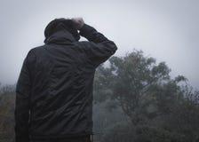 Ένας απομονωμένος απόκοσμος με κουκούλα αριθμός που στέκεται σε μια πορεία στην επαρχία μια ομιχλώδη, βροχερή ημέρα Με χαμηλωμένο στοκ εικόνα με δικαίωμα ελεύθερης χρήσης