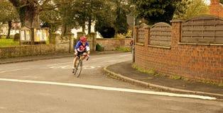 Ένας απομονωμένος ποδηλάτης αγωνίζεται να προφθάσει τους ηγέτες. Στοκ Εικόνες